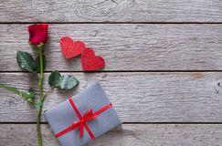 Fondo del biglietto di S. Valentino con il fiore della rosa rossa, i cuori di carta e la scatola attuale su legno rustico Immagini Stock