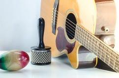 Fondo del blanco de la música de los accesorios de la percusión de la guitarra acústica Foto de archivo libre de regalías