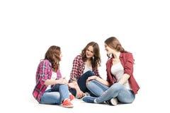 Fondo del blanco del sittingover de tres mujeres jovenes fotografía de archivo