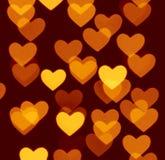 Fondo del bokeh del corazón, objetos borrosos de la foto, amarillos en marrón oscuro Fotos de archivo