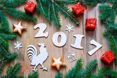 Fondo 2017 del buon anno con 2017 figure, giocattoli di Natale, rami di albero dell'abete e simboli 2017 del nuovo anno del gallo Fotografia Stock