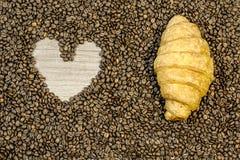 Fondo del chicco di caffè con cuore ed il croissant sulla tavola Fotografia Stock