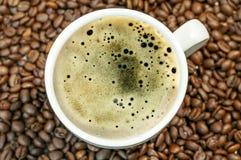 Fondo del chicco di caffè con la tazza della fine calda fresca del caffè Immagini Stock