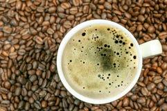 Fondo del chicco di caffè con la tazza della fine calda fresca del caffè su Fotografie Stock