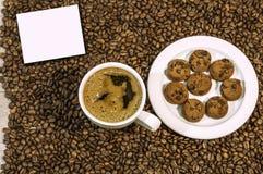 Fondo del chicco di caffè con la tazza di caffè e del piatto caldi freschi in pieno dei biscotti Fotografie Stock Libere da Diritti