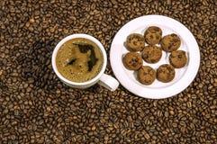 Fondo del chicco di caffè con la tazza di caffè e del piatto caldi freschi in pieno dei biscotti Immagine Stock