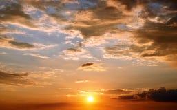 Fondo del cielo de la puesta del sol con las nubes, los colores bajos del sol, rojo oscuro y azules Imágenes de archivo libres de regalías