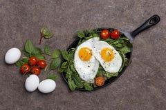 Fondo del concepto con los huevos fritos, los tomates de cereza y el verde fresco imagen de archivo