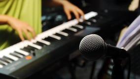 Fondo del concepto de la banda de la música Micrófono del foco selectivo y el jugar borroso del hombre almacen de video