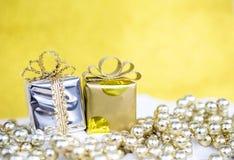 Fondo del concepto de la Navidad de la caja de regalo brillante del primer con la cinta del oro en gotas brillantes Foto de archivo