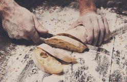 Fondo del concepto de la panadería Manos que cortan rebanadas del pan del pan Fotografía de archivo libre de regalías