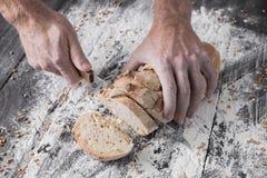 Fondo del concepto de la panadería Manos que cortan rebanadas del pan del pan Fotos de archivo