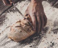 Fondo del concepto de la panadería Manos que cortan rebanadas del pan del pan Imagen de archivo libre de regalías