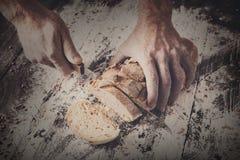Fondo del concepto de la panadería Manos que cortan rebanadas del pan del pan Foto de archivo