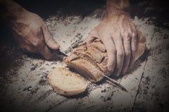Fondo del concepto de la panadería Manos que cortan rebanadas del pan del pan Imagen de archivo