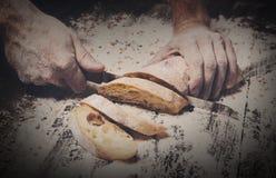 Fondo del concepto de la panadería Manos que cortan rebanadas del pan del pan Imagenes de archivo
