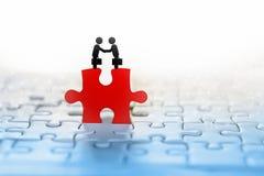 Fondo del concepto del negocio con el icono del apretón de manos de dos hombres de negocios en el rompecabezas rojo con la conexi imágenes de archivo libres de regalías