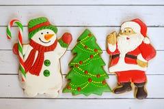 Fondo del día de fiesta del Año Nuevo de la Navidad Galletas del pan de jengibre, Santa Claus, muñeco de nieve, Papá Noel y árbol Imagen de archivo libre de regalías