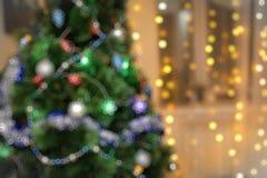 Fondo del día de fiesta de Blured con el árbol de navidad verde y las luces de oro Foto de archivo