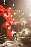 Fondo del día de fiesta con los vidrios de vino rojo, de vino rojo y de ornamentos de la Navidad en la tabla de madera Fotografía de archivo libre de regalías