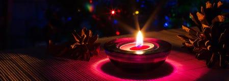 Fondo del día de fiesta de la Navidad con la vela púrpura y las luces coloridas con el copyspace Fotos de archivo libres de regalías