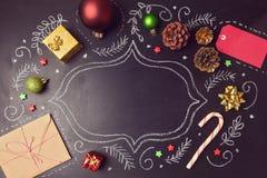 Fondo del día de fiesta de la Navidad con las decoraciones y los dibujos de la mano en la pizarra Visión desde arriba Foto de archivo libre de regalías
