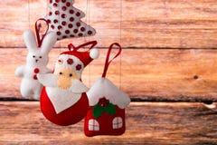 Fondo del día de fiesta de la Navidad con Santa Claus, el conejito, la casa, la picea, las decoraciones y los juguetes Imagenes de archivo