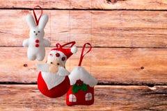Fondo del día de fiesta de la Navidad con Santa Claus, el conejito, la casa, la picea, las decoraciones y los juguetes Fotos de archivo