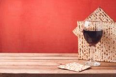Fondo del día de fiesta de la pascua judía con la copa de vino y el matzoh en la tabla de madera Imagenes de archivo