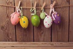 Fondo del día de fiesta de Pascua con las decoraciones de los huevos que cuelgan en cuerda Foto de archivo