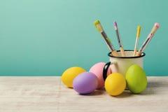 Fondo del día de fiesta de Pascua con los huevos y los cepillos pintados hechos a mano Foto de archivo libre de regalías
