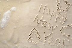 Fondo del día de fiesta - Feliz Año Nuevo y árbol de navidad, escritos en una playa arenosa tropical Fotografía de archivo libre de regalías