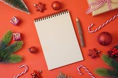 Fondo del día de fiesta de la Navidad con el cuaderno y decoraciones en el re imagenes de archivo