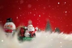 Fondo del día de fiesta de la Navidad con Papá Noel y las decoraciones Paisaje de la Navidad con los regalos y la nieve Feliz Nav Foto de archivo libre de regalías