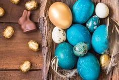 Fondo del día de fiesta de Pascua Pascua coloreó los huevos, los conejitos del chocolate y los dulces en espacio de madera rústic Fotos de archivo