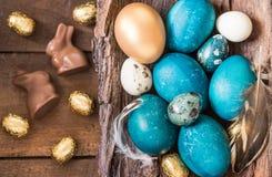 Fondo del día de fiesta de Pascua Pascua coloreó los huevos, los conejitos del chocolate y los dulces en fondo de madera rústico Foto de archivo