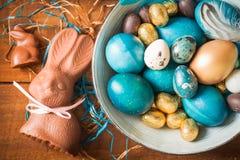 Fondo del día de fiesta de Pascua Pascua coloreó los huevos, los conejitos del chocolate y los dulces en fondo de madera rústico Imagen de archivo