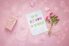 Fondo del día de madres con el mensaje, las rosas rosadas y la caja de regalo encendido Fotografía de archivo