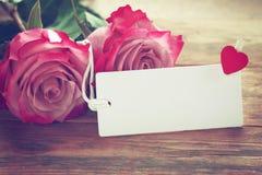 Fondo del día de tarjeta del día de San Valentín, dos rosas rosadas, etiqueta vacía blanca imagenes de archivo
