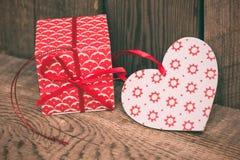 Fondo del día de tarjetas del día de San Valentín con la caja de regalo y corazón rojo en de madera fotos de archivo libres de regalías