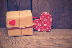 Fondo del día de tarjetas del día de San Valentín con la caja de regalo y corazón rojo en de madera foto de archivo