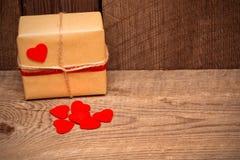 Fondo del día de tarjetas del día de San Valentín con la caja de regalo y corazones rojos en de madera imagenes de archivo