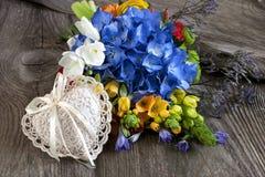 Fondo del día de tarjetas del día de San Valentín con las flores coloridas y corazón decorativo en la tabla de madera Fotos de archivo libres de regalías