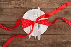 Fondo del día del ` s de la tarjeta del día de San Valentín, placa blanca, bifurcación, cuchillo, corazones de la cinta en la tab Fotografía de archivo