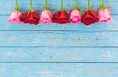 Fondo del día del ` s de la boda o de la tarjeta del día de San Valentín con la frontera roja y rosada de las rosas en la madera  Foto de archivo libre de regalías