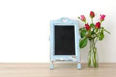 Fondo del día del ` s de la tarjeta del día de San Valentín, rosas rojas y chalkboa en blanco del vintage Fotografía de archivo