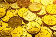Fondo del día del `s del St Patrick Monedas de oro con el trébol bajo sol suave, concepto del día de St Patrick fotos de archivo