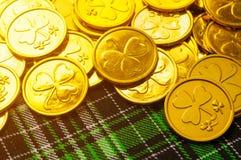 Fondo del día del `s del St Patrick Monedas de oro con el trébol en el paño a cuadros verde de la textura bajo sol suave foto de archivo libre de regalías