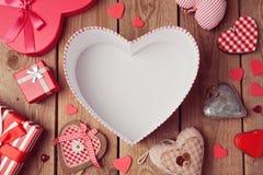 Fondo del día de tarjeta del día de San Valentín con la caja vacía de la forma del corazón en la tabla de madera Visión desde arr Imágenes de archivo libres de regalías