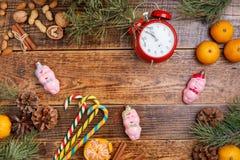 Fondo del fondo de la Navidad con un reloj, los dulces, las bolas de la Navidad y las mandarinas en un fondo de madera imagenes de archivo